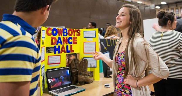 student showing off project involving country line dancing