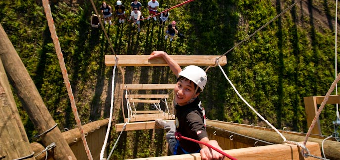 A male student climbing rope ladder at recreation center obstacle course